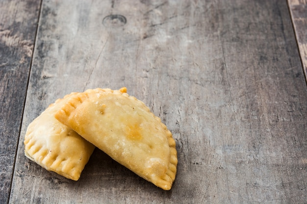 Typical spanish empanadas on wooden table copy space