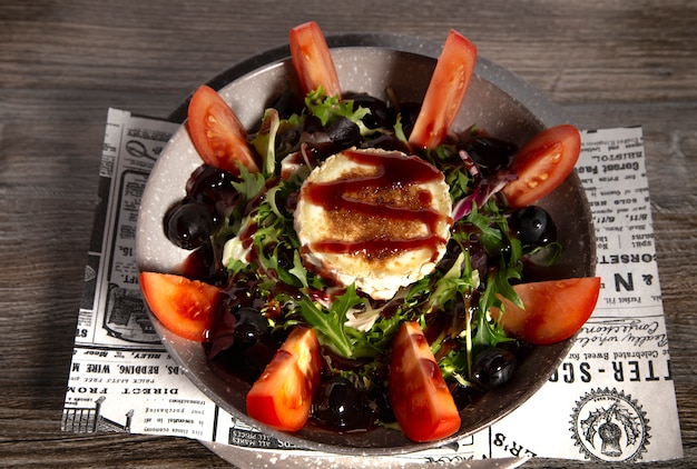 Typical spanish goat cheese salad on wooden background. isolated image
