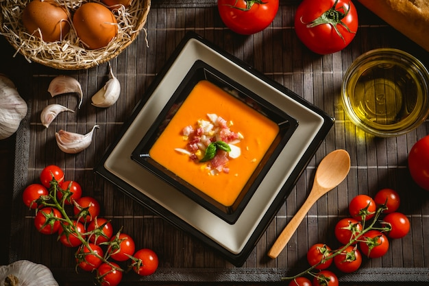 木製のテーブルにいくつかの食材を使った正方形のプレートでコードバンサルモレホの典型的なスペインのレシピ