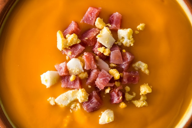ハムと卵の木製のテーブルの上で典型的なスペインのサルモレホクリームをクローズアップ