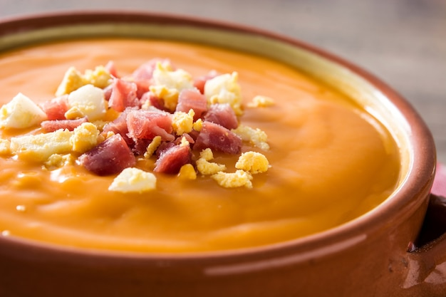 Typical spanish salmorejo cream with ham and egg on wooden table close up