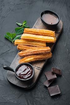 典型的なスペインのスナックチュロス、揚げパンのペストリー、通常はチョコレートキャラメルのホットソースセット、黒の背景