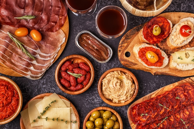 Типичная концепция испанских тапас. в концепцию входят ломтики хамона, чоризо, колбасы, тарелки с оливками, помидорами, анчоусами, пюре из нута, сыром.