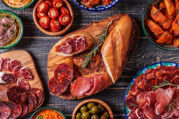 Typical spanish tapas concept. concept include variety slices jamon,  chorizo, salami, bowls with olives,  peppers, anchovies, spicy potatoes, mashed chickpeas