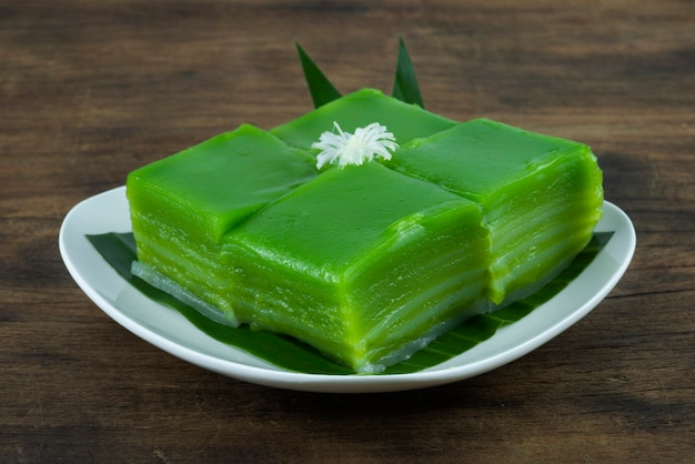 木製の背景の白いプレートに典型的なタイの蒸し緑パンダン層ケーキデザート