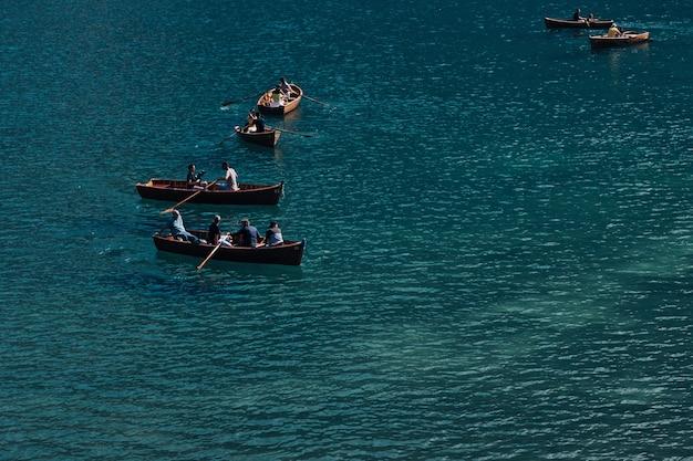 Типичные деревянные лодки с туристами на высокогорном озере. горное озеро.