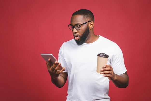 Печатать сообщение удивленный чернокожий человек печатая что-то на мобильном телефоне, выпивая кофе пока стоящ изолированный против красной предпосылки. Premium Фотографии