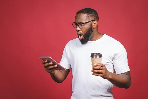 Печатать сообщение удивленный чернокожий человек печатая что-то на мобильном телефоне, выпивая кофе пока стоящ изолированный против красной предпосылки.