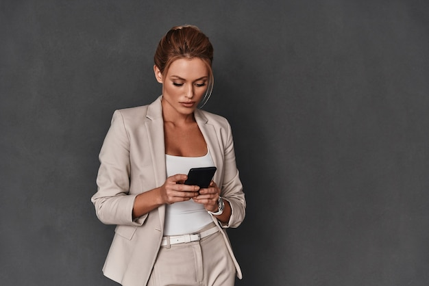Typing business message. attractive young woman in smart casual wear using her smart phone while standing against grey background