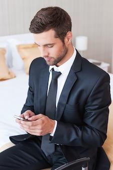 Набрав деловое сообщение. уверенный молодой человек в строгой одежде набирает сообщение на мобильном телефоне, сидя на кровати в гостиничном номере