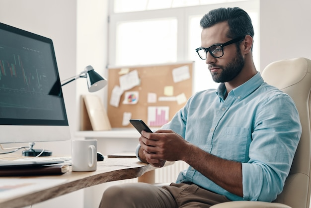 Typing business message. young modern businessman using smart phone while sitting in the office