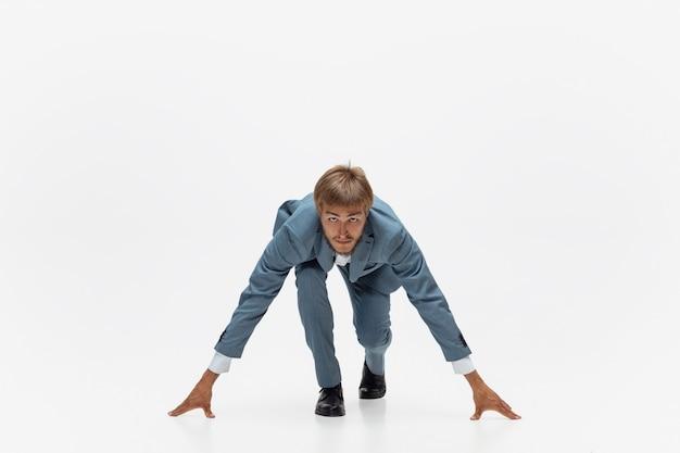タイピング。プロのアスリート、スポーツマンのような白いスペースでジョギングを実行しているオフィス服の男。動きのあるビジネスマン、ボールを持ったアクションの珍しい表情。スポーツ、健康的なライフスタイル、創造性。
