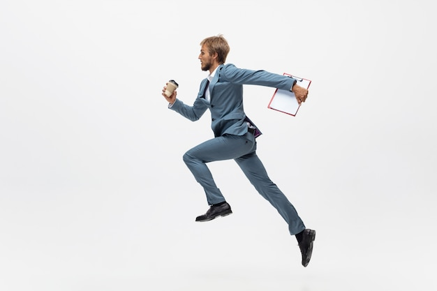 Typing. man in office clothes running, jogging on white space like professional athlete, sportsman. unusual look for businessman in motion, action with ball. sport, healthy lifestyle, creativity.