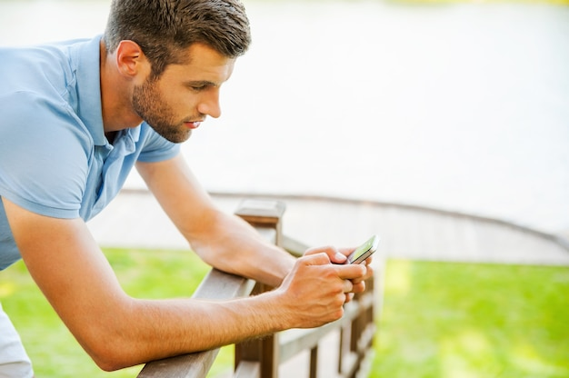 Typing message to friend. side view of handsome young man typing message on mobile phone while standing on the riverbank