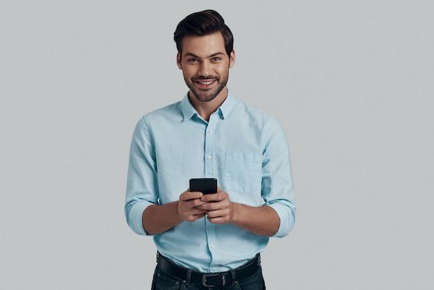 メッセージを入力します。灰色の背景に立ってスマートフォンを使用してカメラを見ているハンサムな若い男