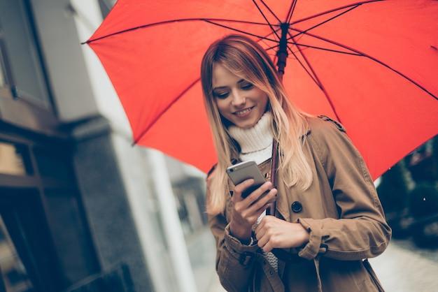 이동 중에 메시지를 입력합니다. 우산을 들고 거리에 서 있는 동안 그녀의 휴대 전화를 보고 매력적인 젊은 웃는 여자