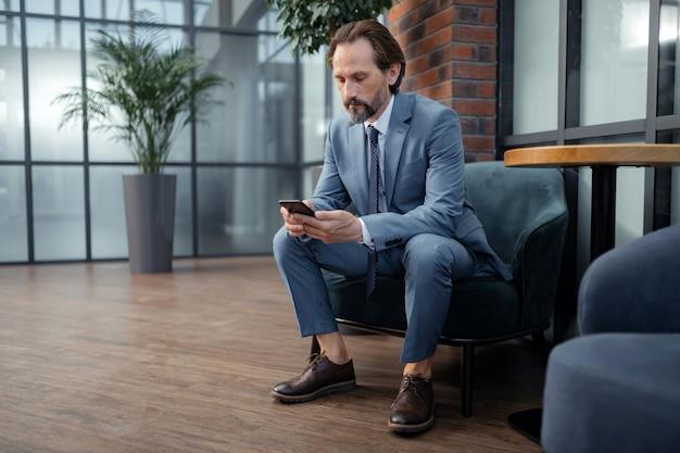 メッセージを入力します。 smarpthoneにメッセージを入力する灰色のスーツを着ているスタイリッシュな成熟したビジネスマン