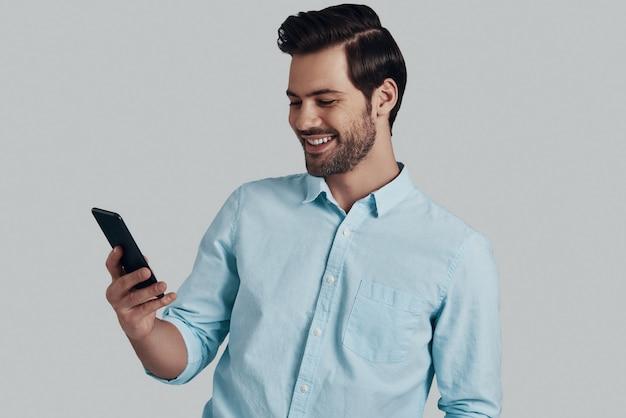 友達にメッセージを入力します。スマートフォンを使用して、灰色の背景に立って笑っているハンサムな若い男