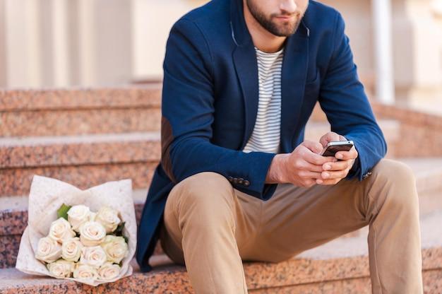 ガールフレンドへのメッセージを入力します。携帯電話を見て、彼の近くに横たわっているバラの花束と階段に座っている間スマートジャケットでハンサムな若い男のクローズアップ