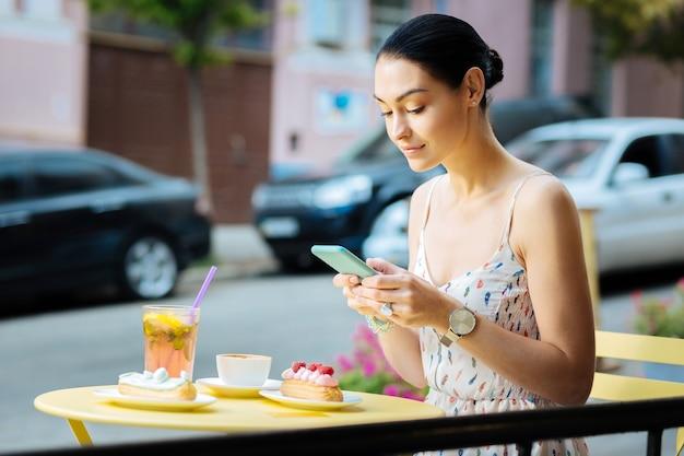 メッセージを入力します。現代のスマートフォンを持って、レモネードとデザートをテーブルに座ってオンラインチャットをしている美しい穏やかな女性