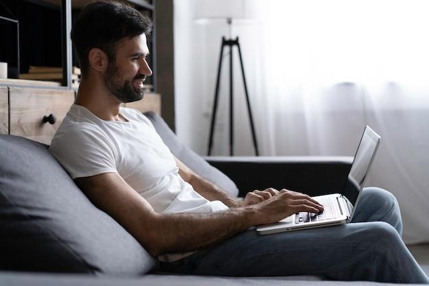 Ввод нового сообщения в блоге. вид сбоку красивого молодого человека, использующего свой ноутбук с улыбкой, сидя на диване у себя дома.