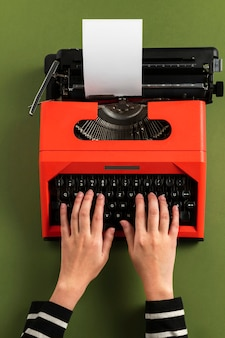 Typing on a red retro typewriter blank paper