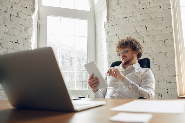 Typing text, analyzing, surfing. caucasian young man in business attire working in office. young businesswoman, manager doing tasks with smartphone, laptop, tablet has online conference, studying.