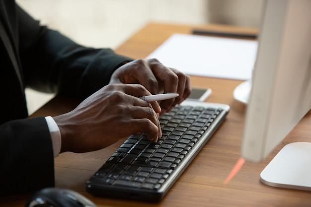 Digitazione del testo, primo piano. imprenditore afroamericano, uomo d'affari che lavora concentrato in ufficio. sembra serio e impegnato, indossa un abito classico.