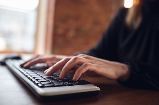 Typing text, close up. caucasian young woman in business attire working in office