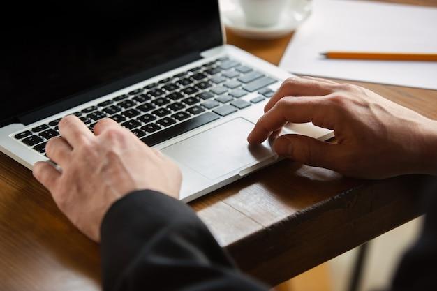 テキストを入力します。オフィスで働いている白人男性の手のクローズアップ。ビジネス、金融、仕事、オンラインショッピングまたは販売の概念。広告用のコピースペース。教育、コミュニケーションフリーランス。
