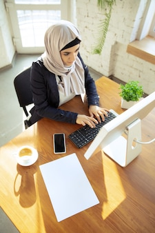 Typing text. portrait of a beautiful arabian businesswoman wearing hijab while working at openspace or office. concept of occupation, freedom in business area, leadership, success, modern solution.