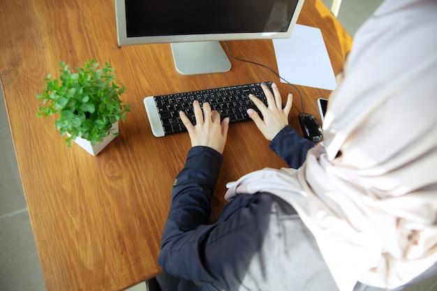 텍스트를 입력합니다. 오픈스페이스나 사무실에서 일하는 동안 히잡을 쓴 아름다운 아라비아 여성 사업가의 초상화. 직업의 개념, 비즈니스 영역의 자유, 리더십, 성공, 현대적인 솔루션.
