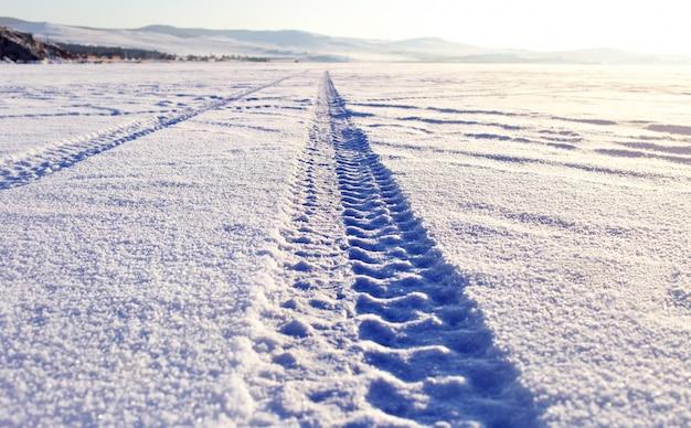 Следы шин в снегу на ледяной поверхности озера байкал