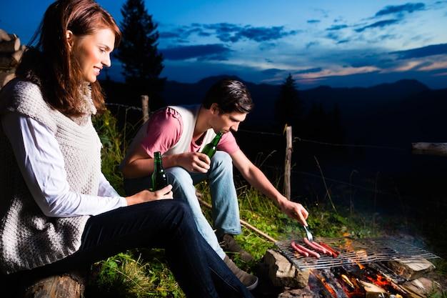 Тироль - молодая пара, сидящая на альпийском лугу горы у костра в баварских альпах, наслаждаясь романтическим вечерним закатом панорамы в свободное время или в отпуске.