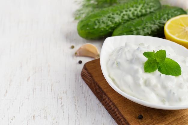 Tzatziki sauce in a bowl and ingredients - cucumber, mint, dill, lemon, garlic