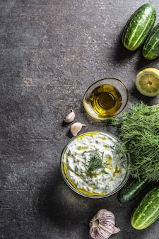 Соус цацики в стеклянной миске укроп огурец оливковое масло лимон и чеснок.