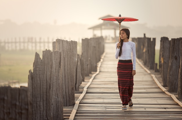 Бирманская женщина, держащая традиционный красный зонт и идущая по мосту u bein