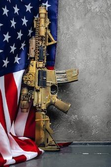 壁の近くの米国の戦闘旗とアサルトライフル。 。
