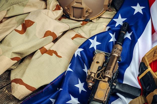 木製のテーブルに米国の戦闘旗とアサルトライフル。