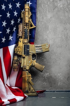 U.s. battle flag and assault rifle near the wall. .