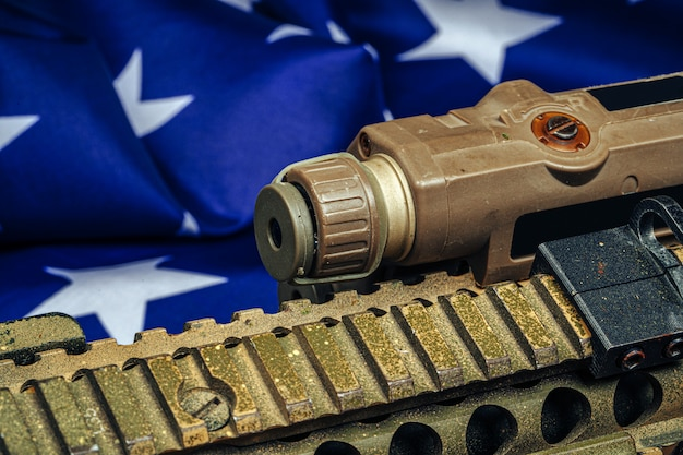U.s. battle flag and assault rifle on the wooden table.