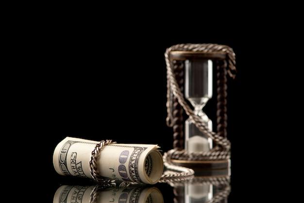 Сша> доллары прикованы к песочным часам с серебряным чаем. черный фон. студийный снимок.