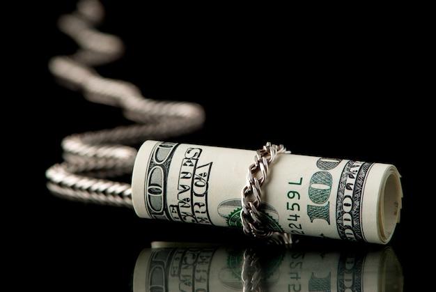 Доллары прикованы серебряной цепью на черном фоне. студийный снимок