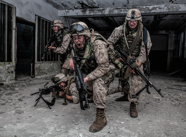 U.s. marines assault squad, commando special detachment, army elite team armed with automatic weapon, yelling and attacking enemy, breaking through with fight, rush with fire during urban firefight