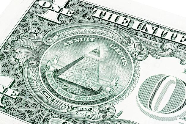 1 доллар сша на фото крупным планом. малая глубина резкости. око провидения, всевидящее око бога, логотип мейсон иллюминатов, пирамида, треугольник. великая печать.