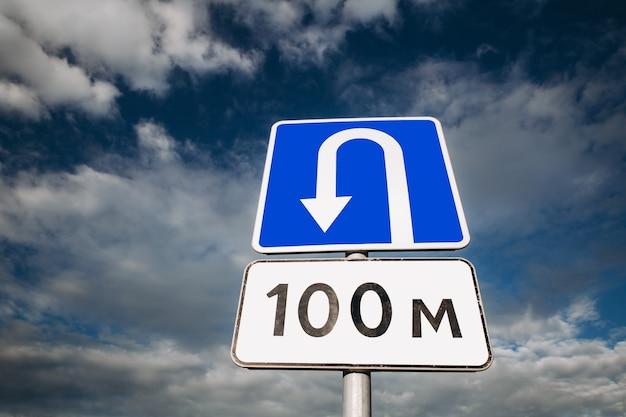 Разверните дорожный знак места на голубом небе с облаками. неправильный поворот.