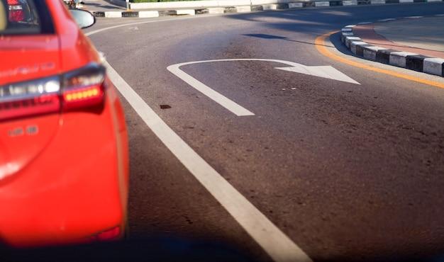 U turn or reverse lane sign on traffic road surface