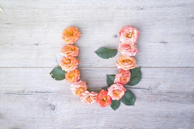 U、灰色の花のアルファベットは、灰色の木製の背景に、フラットなレイアウト