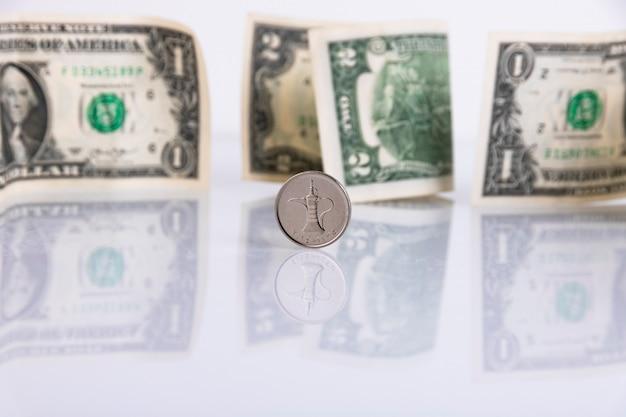 紙の米ドルを背景にしたuae通貨ディルハムコイン。スペースをコピーします。