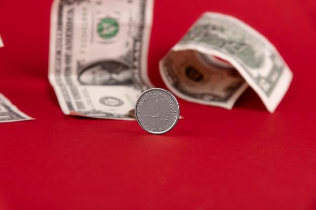 アラブ首長国連邦の通貨ディルハムコイン、紙の米ドルと赤い背景に対して設定されます。スペースをコピーします。